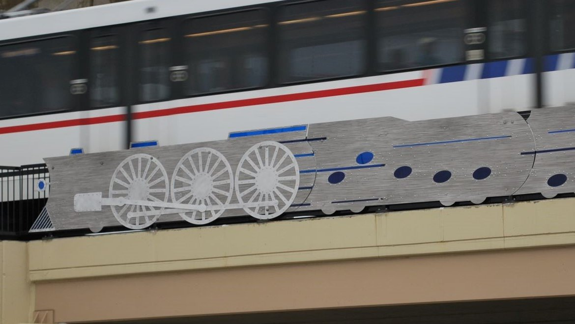 "Blue Train is a public art sculpture by artist Clark Wiegman that is installed on the Vandeventer Avenue MetroLink Bridge. The piece is an abstracted train and locomotive with the opening 8 bars of ""St. Louis Blues"" depicted as a series of blue notes."