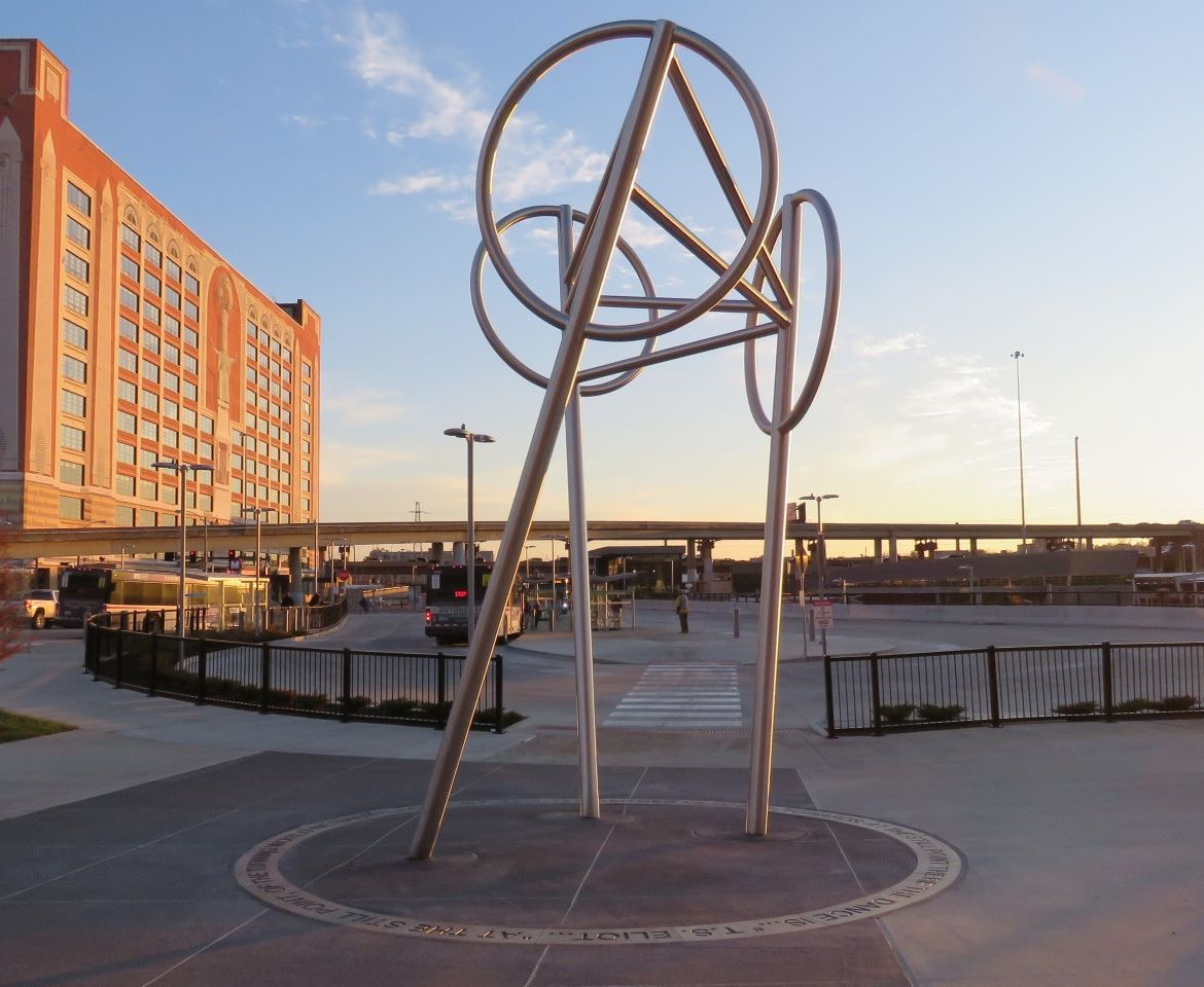 Wheels is a public art sculpture by artists Bill Baker and Claudia Cuesta located at the Civic Center Transit Center. The sculpture is a symbol of the movement and life of people, trains, buses, and the city. The sculpture is ringed with a poem by T.S. Eliot.