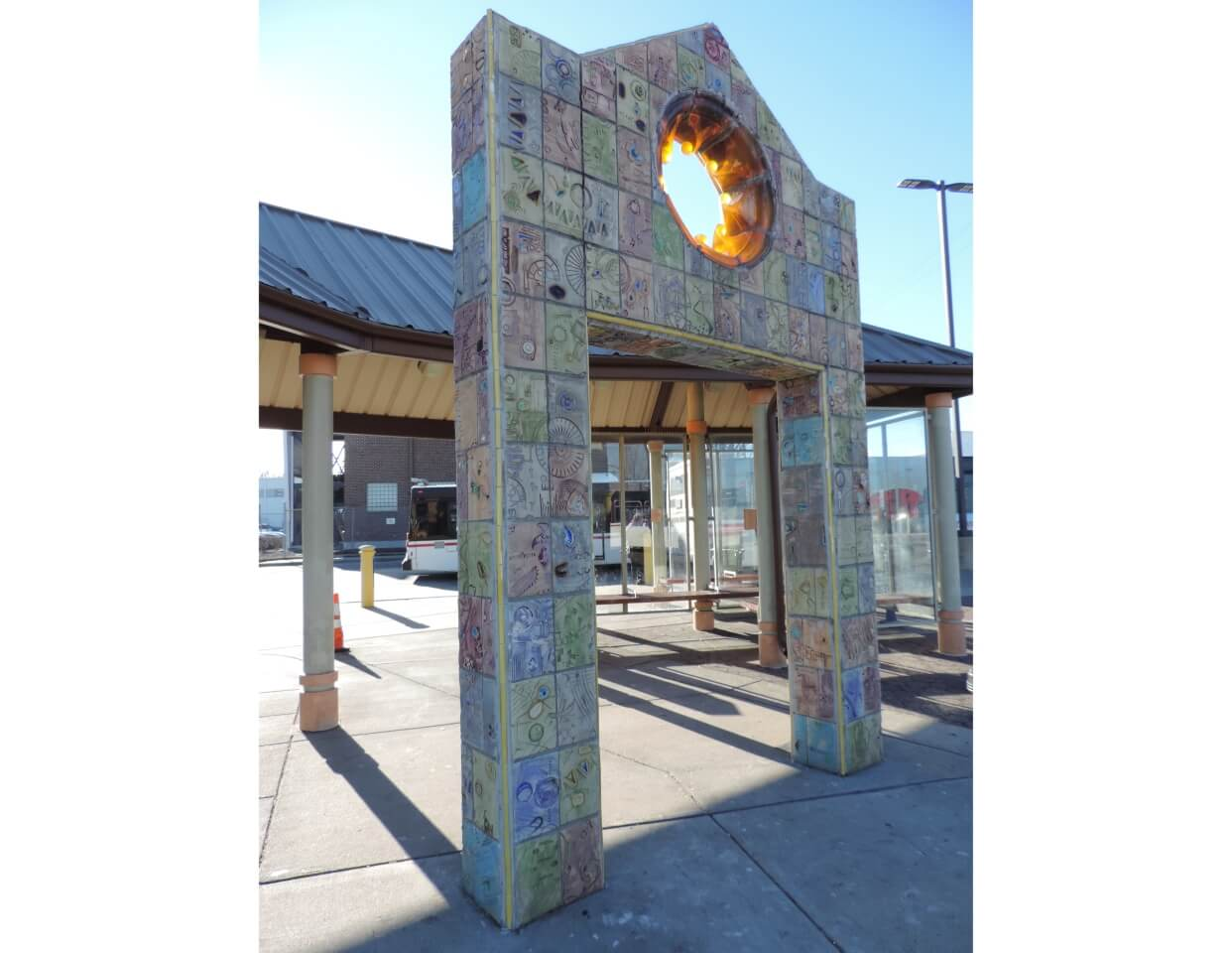 Metroglyph Portal is a public art sculpture created by Con Christeson and Phil Robinson. The concrete gateway is veneered in tiles impressed with textures and patterns from spare bus parts. A glowing resin mandala is the central focus of the piece.