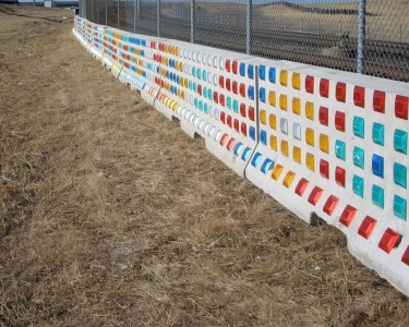 St. Louis Rhythm is light-activated public artwork by artist Richard Elliot located along the MetroLink Right of Way near Interstate 70. The patterned artowk is composed of road reflectors attached to concrete Jersey barriers.
