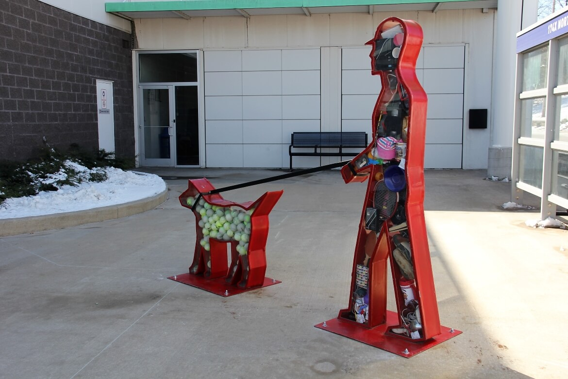 I Want was created by artist Victoria Fuller and is currently installed at the North County Transit Center. The silhouetted figures of a man walking his dog are filled with everyday consumer objects.