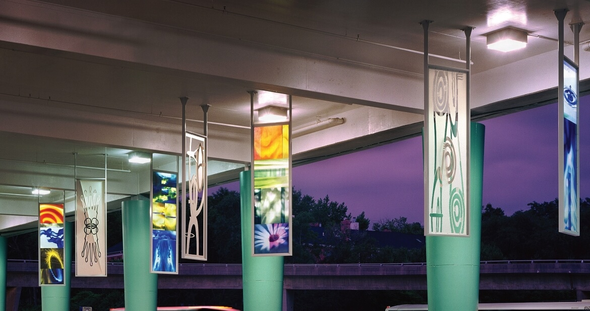 Oasis is an aluminum and laminated glass sculpture installed overhead at the Clayton MetroBus Center that was created by Catherine Woods. The panels symbolize the four basic alchemical elements (earth, air, fire, and water) as well as a fifth element rooted in the concept of good luck.